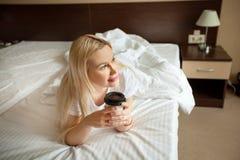 Piękna młoda dziewczyna w łóżku z filiżanką zdjęcie stock