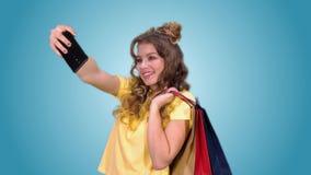 Piękna młoda dziewczyna w żółtej koszulce po tym jak robić zakupy zrobi selfie i ono uśmiecha się zbiory