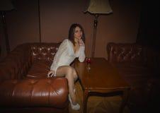 Piękna młoda dziewczyna w białej sukni z szkłem wino, zdjęcia stock