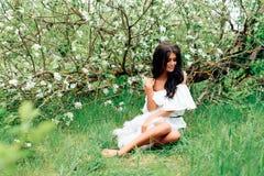 Piękna młoda dziewczyna w biel sukni w wiośnie kwitnie jabłczanych sady Fotografia Stock
