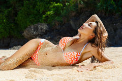 Piękna młoda dziewczyna w bikini na tropikalnej plaży Błękitny morze wewnątrz Zdjęcia Stock