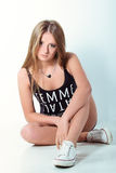 Piękna młoda dziewczyna w cajgach zwiera i sporta Obuwiany obsiadanie w studiu na błękitnym tle fotografia royalty free