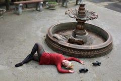 Piękna młoda dziewczyna w czerwonej mini sukni przy mumiowatą fontanną Zdjęcie Royalty Free
