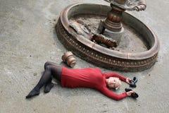 Piękna młoda dziewczyna w czerwonej mini sukni przy mumiowatą fontanną Zdjęcie Stock