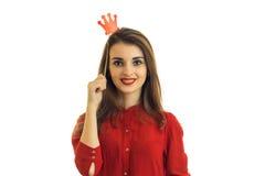Piękna młoda dziewczyna w czerwonej sukni patrzeje prostych uśmiechy i utrzymuje blisko włosianych wsparć w postaci korony Obraz Stock