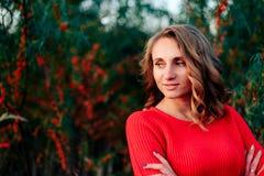 Piękna młoda dziewczyna w czerwonym pulowerze i niebieskich dżinsach przy zmierzchem na tle buckthorn i greenery Zdjęcie Royalty Free