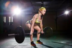 Piękna młoda dziewczyna w gym trenuje mięśnie nogi i plecy, deaet ćwiczy deadlift, siedzi z ciężarem, chwyty zakazuje i Obrazy Stock