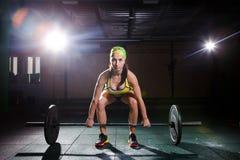 Piękna młoda dziewczyna w gym trenuje mięśnie nogi i plecy, deaet ćwiczy deadlift, siedzi z ciężarem, chwyty zakazuje i Fotografia Stock