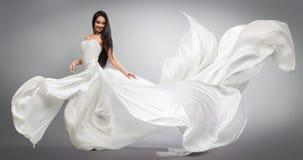 Piękna młoda dziewczyna w latać biel suknię tkaniny spływanie Lekki biały sukienny latanie obraz stock