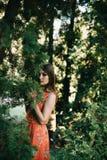 Piękna młoda dziewczyna w lato czerwieni sukni w parku Fotografia Royalty Free