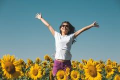 Piękna młoda dziewczyna W okularów przeciwsłonecznych stojakach W słonecznikach Z rękami Up I ono Uśmiecha się Zdjęcie Stock