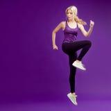 Piękna młoda dziewczyna w poza biegaczu Pracowniany tło, purpura obraz royalty free
