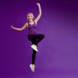 Piękna młoda dziewczyna w poza biegaczu Pracowniany tło, purpura szczęśliwy jumping zdjęcie royalty free