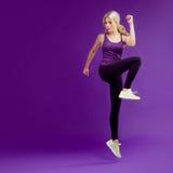 Piękna młoda dziewczyna w poza biegaczu Pracowniany tło, purpura szczęśliwy jumping zdjęcia stock