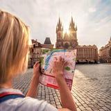 Piękna młoda dziewczyna w Praga spojrzeniach przy miasto mapą Obrazy Stock
