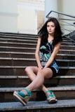 Piękna młoda dziewczyna w sukni siedzi na schodku Zdjęcie Royalty Free
