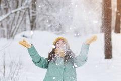 Piękna młoda dziewczyna w trykotowym kapeluszu rzuca śnieg w zima lesie zdjęcie stock