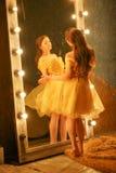 Piękna młoda dziewczyna w wieczór sukni złocistych stojakach na futerkowym dywaniku blisko ampuły lustra w ramie z światłami i sp zdjęcia stock