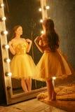 Piękna młoda dziewczyna w wieczór sukni złocistych stojakach na futerkowym dywaniku blisko ampuły lustra w ramie z światłami i sp obraz stock