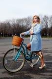 Piękna młoda dziewczyna z błękitnym bicyklem Zdjęcia Stock