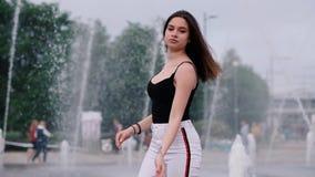 Piękna młoda dziewczyna z ciemnym włosy przy fontanną swobodny ruch zbiory wideo