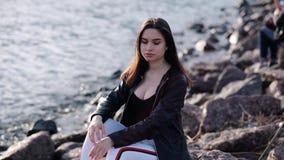 Piękna młoda dziewczyna z ciemnym włosy przy nadmorski Zmierzchu ?wiat?o swobodny ruch zbiory
