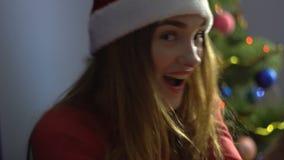 Piękna młoda dziewczyna z czerwonymi wargami w Santa kapeluszowym tanu i mieć zabawie piłek bożych narodzeń odosobniony nastroju  zdjęcie wideo