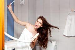 Piękna młoda dziewczyna z długim czarni włosy w białym ręczniku i suszy włosy z hairdryer Zdjęcie Stock