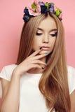 Piękna młoda dziewczyna z długim prostym włosy z jaskrawego kwiatu kapitałką Fotografia Royalty Free