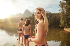 Piękna młoda dziewczyna z przyjaciółmi przy jeziorem Zdjęcie Royalty Free