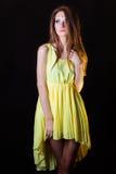 Piękna młoda dziewczyna z sztuka makijażem usuwa w studiu na czarnym tle w żółtej sukni zdjęcia stock