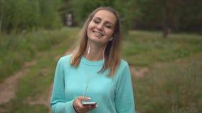 Piękna młoda dziewczyna z telefonem w rękach słucha muzyka z hełmofonami i ono uśmiecha się przy kamerą plenerową zdjęcie wideo