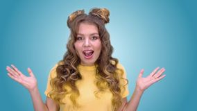 Piękna młoda dziewczyna z tytułowań przedstawieniami zaskakuje ona i rozprzestrzenia ręki zdjęcie wideo