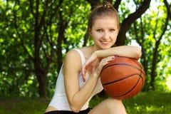 Piękna młoda dziewczyna z uśmiechem, siedzi z koszykówki piłką wewnątrz dla sportów obraz stock
