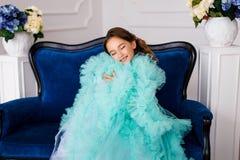 Piękna młoda dziewczyna z zamkniętymi oczami w luksusowym turkus sukni obsiadaniu na luksusowym błękitnym przytuleniu i leżance s Zdjęcia Stock