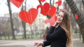 Piękna młoda elegancka dziewczyna bawić się z papierową serce dekoracją w jesień parku celabrating pojęcie dobiera się dzień szcz zdjęcie wideo