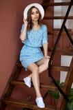 Piękna młoda europejska kobieta w błękit sukni ang światła kapeluszu siedzi na schodkach w domu, dosyć caucasian potomstwa zdjęcia stock