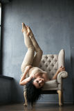 Piękna młoda gimnastyczka na krześle wziąć niezwykłą mody pozę Zdjęcia Stock