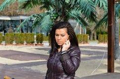 Piękna młoda gniewna brunetka opowiada na telefonie Fotografia Royalty Free