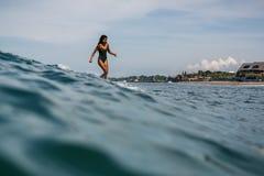 Piękna młoda indonezyjska kobieta w bikini surfingu fala w Bali na tle niebieskie niebo, chmury i tropikalna plaża, obraz royalty free