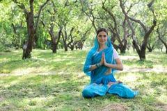 Piękna młoda indyjska kobieta ubierał w sari medit i modleniu zdjęcia stock