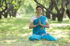 Piękna młoda indyjska kobieta ubierał w sari medit i modleniu obrazy royalty free