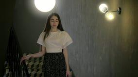 Piękna młoda Kaukaska dziewczyna patrzeje kamera styl życia z długim ciemnym włosy elegancko iść puszek schodki zbiory