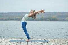 Piękna młoda kobieta ćwiczy joga asana Ardha Chakrasana - Przyrodnia koło poza na drewnianym pokładzie blisko jeziora obraz stock