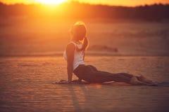 Piękna młoda kobieta ćwiczy joga asana Urdhva Mukha Svanasana - oddolny obszycie pies w pustyni przy zmierzchem obrazy royalty free