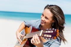Piękna młoda kobieta bawić się gitarę na plaży Obrazy Stock