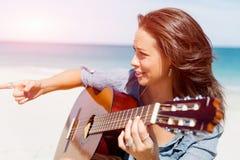 Piękna młoda kobieta bawić się gitarę na plaży Zdjęcia Stock