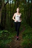 Piękna młoda kobieta biega w lesie - aktywny biegacza bieg Obrazy Royalty Free