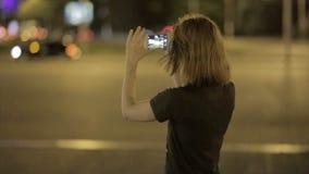 Piękna młoda kobieta bierze obrazek na smartphone przy nocy ulicą zdjęcie wideo
