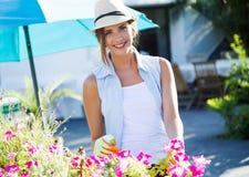 Piękna młoda kobieta bierze opiekę ogrodowy dom Zdjęcie Stock